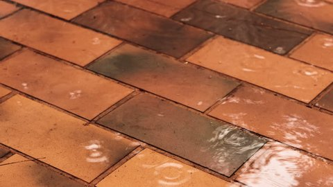 Rain dripping on old terracotta color floor tiles, close up