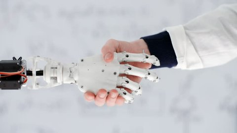 Male hand of scientist inventor shakes robotic arm on background white board