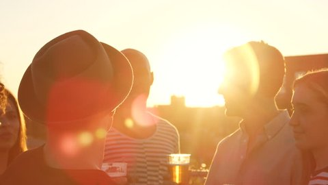 Friends making a toast on a rooftop at sundown, close up