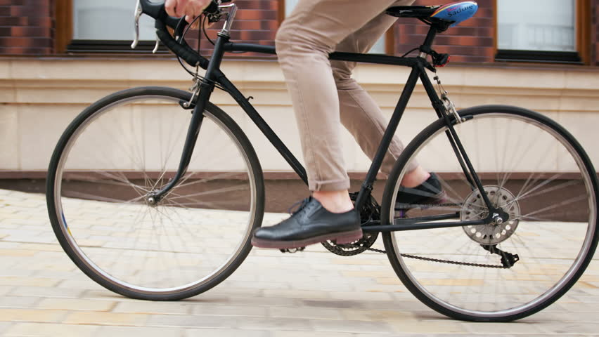 4k low angle video of stylish hipster man riding black sports bicycle on street