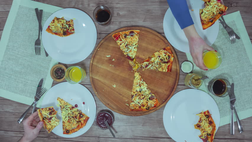 Top view of Hands taking pizza cuts from plate on the table. Time lapse 4K