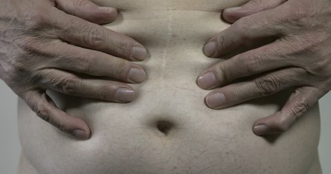 Mature man touching his stomach and showing a scar