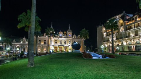 Square with Grand Casino in Monte Carlo night hyperlapse timelapse, Monaco. Historical buildings around. Palms on the side. Parking and traffic on the road