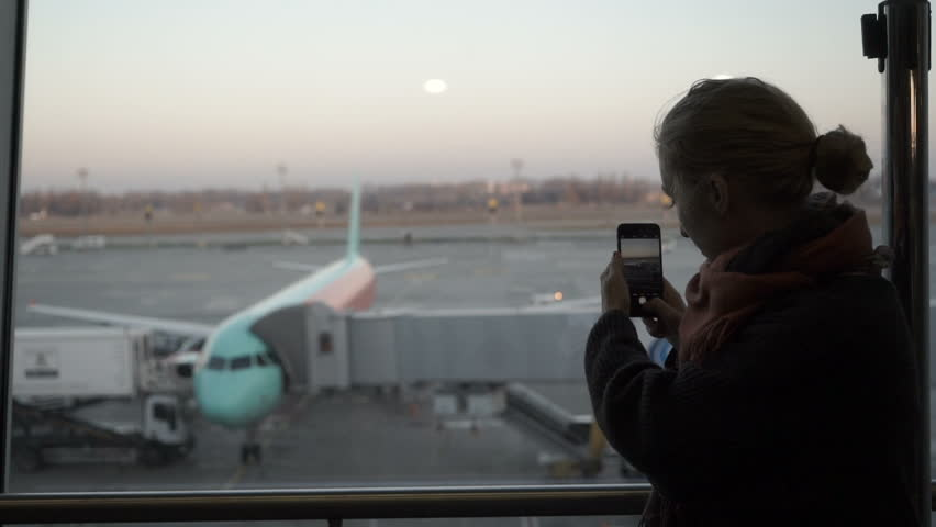Handsome girl standing beside glass wall in modern airport terminal, taking photo picture of airplane aircraft, travelling to other countires.
