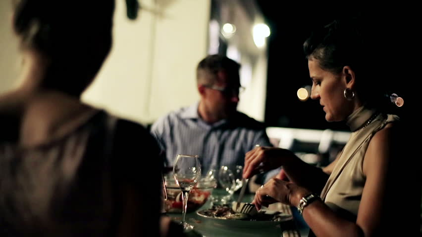 Group of friends celebrating dinner on the terrace at night, steadycam shot  #3471977