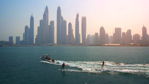 Two waterskiers towed by a speedboat. against the backdrop of Dubai's modern. urban skyline in the late afternoon. UltraHD 4k footage