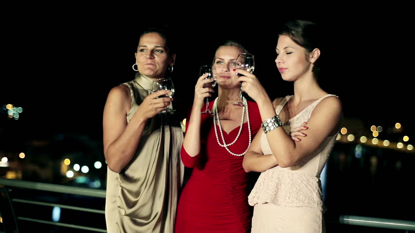 Three female friends enjoying night party on the terrace, crane shot