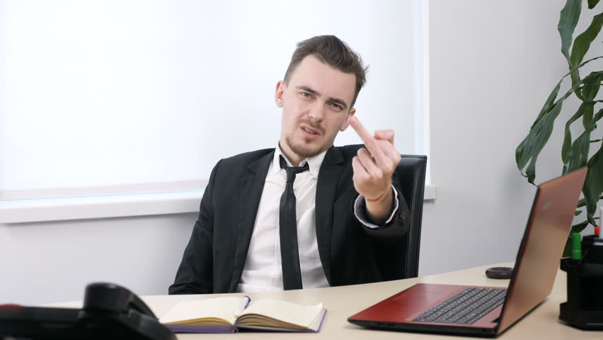 Young businessman in suit sitting in office and showing fuck sign 60 fps