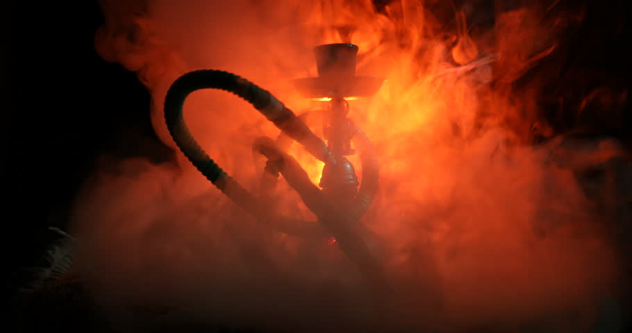 Hookah hot coals on shisha bowl on orange (like fire) clouds of steam on dark background. Stylish oriental shisha. Shisha Concept. On rotating display.