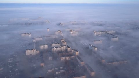 Aerial view of cityscape in smoke and fog.  Beautiful view from bird's eye view to very dense morning fog over city. Smog or fog in the city. Problem of pollution of the environment by smoke and smog.