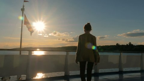 Woman silhouette standing on deck of cruise ship and looking at landscape. Sunset light, golden hour. Nature and journey concept