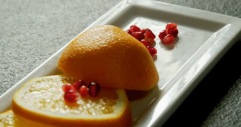 Close-up of slice of orange with pomegranate seeds in tray on grey background 4K 4k