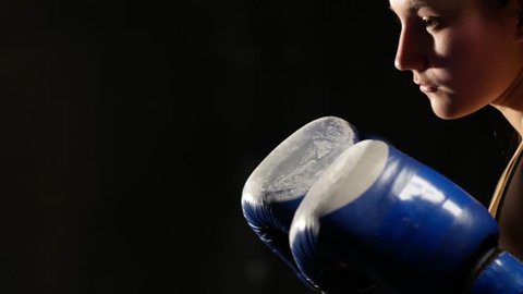 Young woman fighter mma in boxing gloves hitting on punching bag