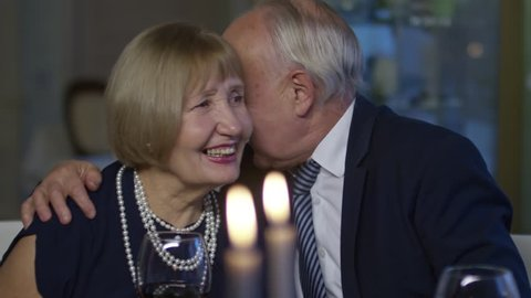 PAN of elderly man hugging laughing senior woman and whispering compliments in her ear during date in restaurant