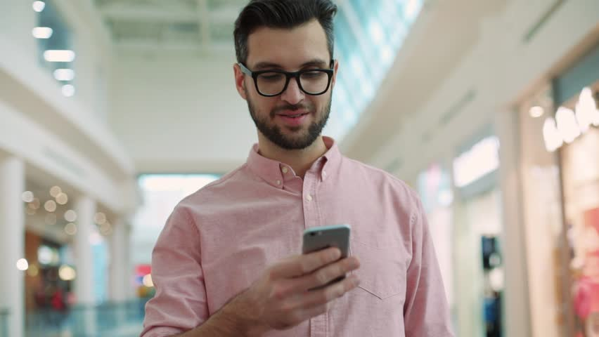 Portrait handsome young man wear glasses stand use phone smiling feel happy in mall shopper hand person shopping business communication professional attractive sms businessman slow motion | Shutterstock HD Video #34792402