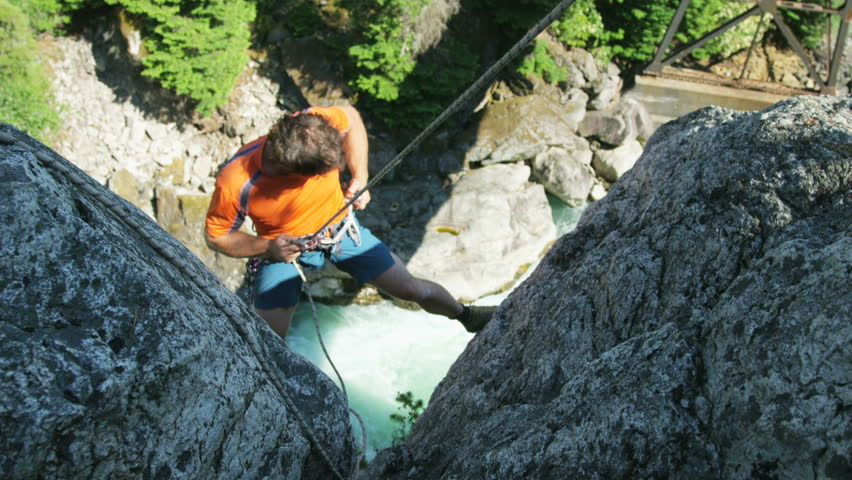 Confident Caucasian American male climber wearing safety equipment on the rocky extreme wall in Squamish Valley Canada RED WEAPON | Shutterstock HD Video #34798312