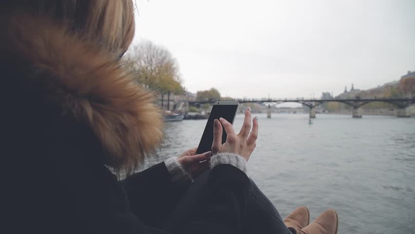 Cute girl using cellphone with Seine river in the background, Paris - France. | Shutterstock HD Video #34821625