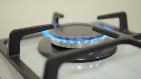Natural gas inflammation in stove burner, close up view. gas burning from a kitchen gas stove