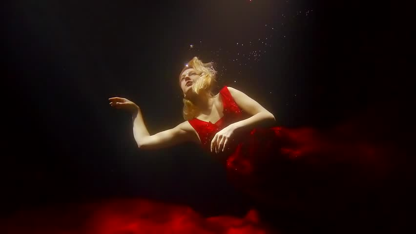 a young woman in a red wedding dress is floating under the water, she is at sea depth