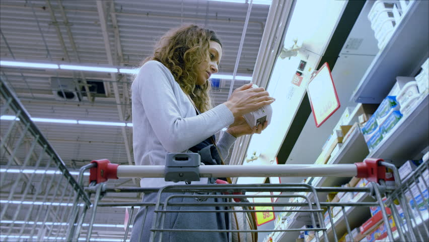 Young woman chooses the butter in the supermarket, 4K. | Shutterstock HD Video #34842778