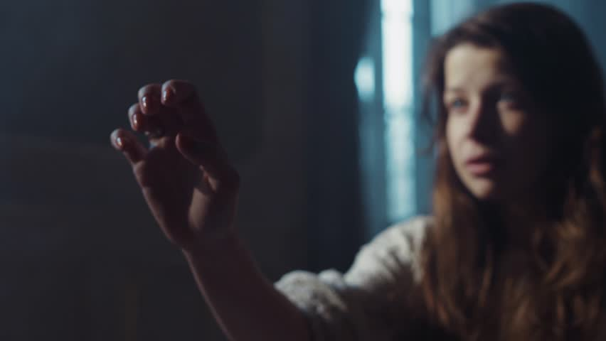 Insane like girl with shabby hair holds her hand, as trying to touch someone. No people around. Paranormal, moody atmosphere. Morning sun lighting the room