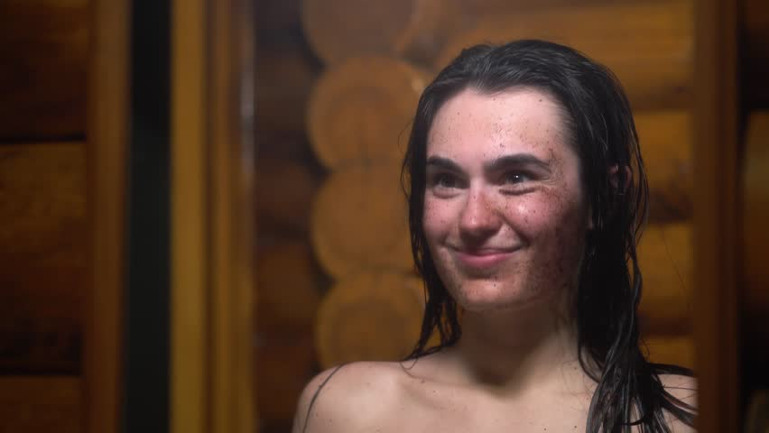 Brunette young girl after sauna happy and smiling applies coffee scrub on her face looking in the mirror