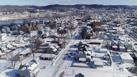 A slow forward winter aerial establishing shot of snow covered roads and homes in a rust belt residential neighborhood. Rochester and Ohio River in the distance. Pittsburgh suburbs.