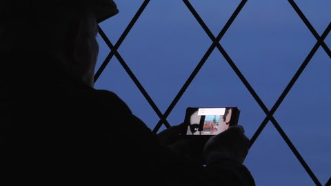 Senior man takes photo of cityscape of Lubeck from the observation deck