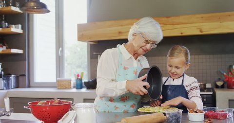 Happy grandmother and granddaughter preparing pie in the kitchen 4k