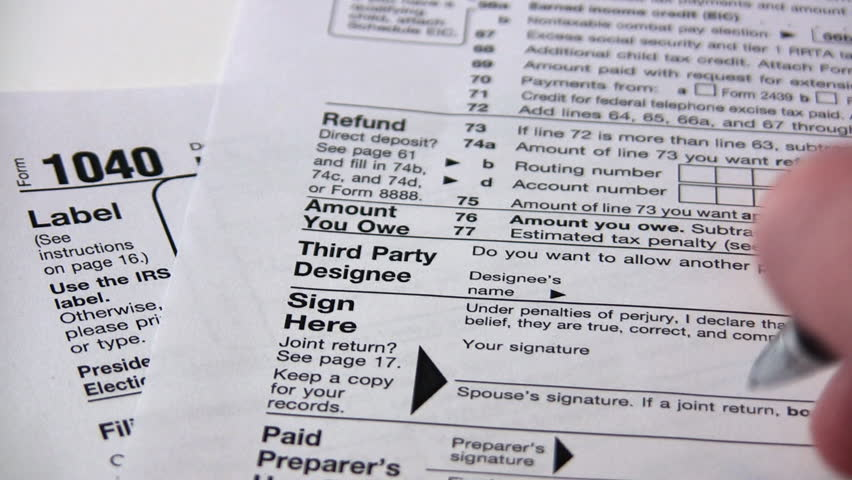 Signing a 1040 income tax return form.