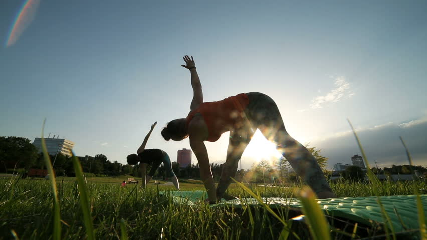 Yoga at park. Two girls exercising outdoors. Concept of healthy lifestyle. | Shutterstock HD Video #34896232