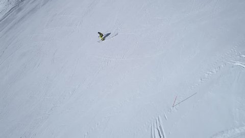 Aerial - Side view tracking shot of good alpine skier skiing down the wide empty ski slope