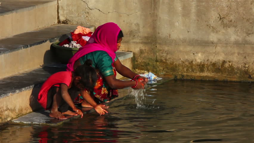 UDAIPUR, INDIA - NOVEMBER 24, 2012: Indian woman washing clothes in the lake in Udaipur, India, 24 nov 2012