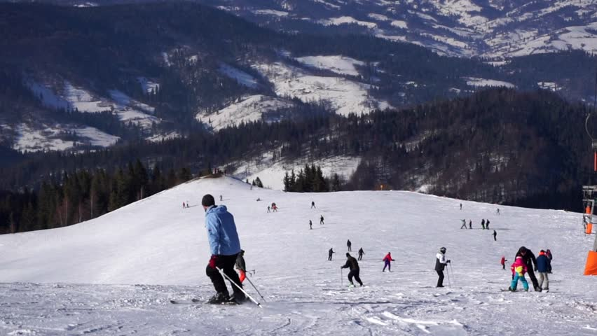 A male skier silhouette in a ski suit slowly skiing downhill between other skiers on a forest background. Ski resort in the snowy mountain woods on a bright winter day.