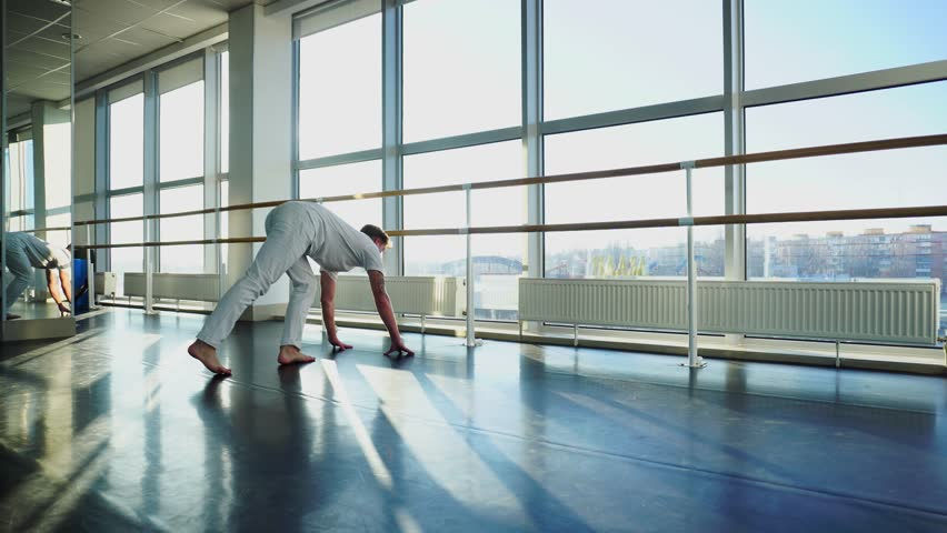 Young business man recently start going to gym, guy trying insistently to stand on hands. Tattooed fair-haired male wearing white sportswear. Concept of well-equipped modern hall, sport clothes or | Shutterstock HD Video #34918612