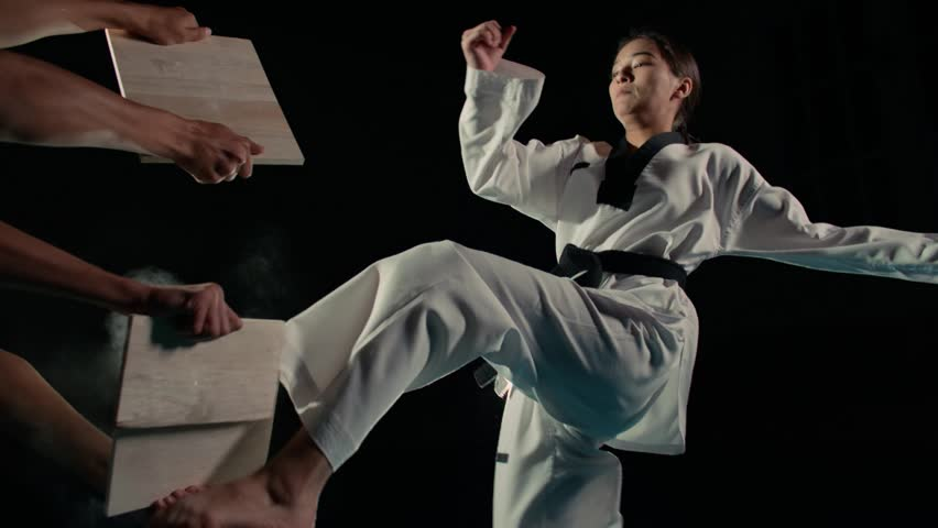 Asian beautiful girl fighter practicing to break the board with a kick of the feet, slow motion