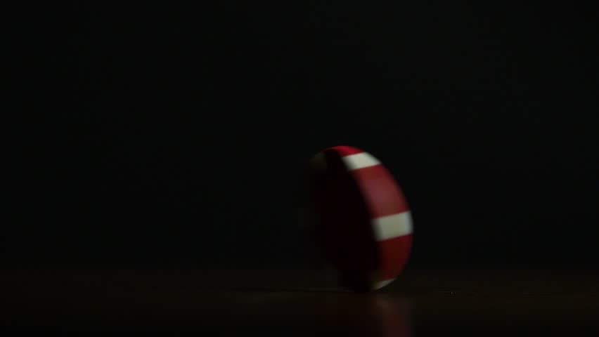 Cinemagraph - Rotation of poker chips on the table isolated on black background. Poker chips shaffling. Poker chip spinning on the table isolated on dark background