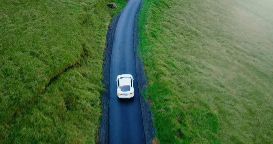 Cinematic aerial view of electric car driving on country road at sunset #34949602