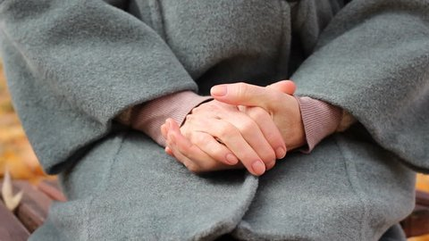 Elder ill woman outside in park in psychiatric hospital, rubbing hands nervously