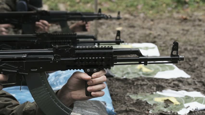 Slow motion soldier shooting from a machine gun on a shooting range
