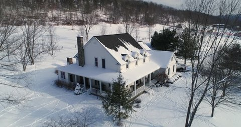 A slow dollying down establishing shot of a typical snow-covered farmhouse in rural Pennsylvania in the winter.