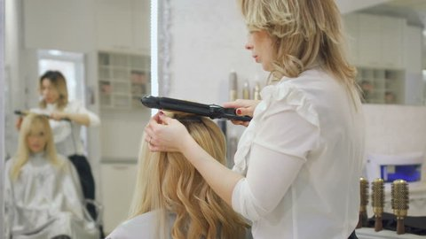 Hairdresser curls blonde hair with curling iron