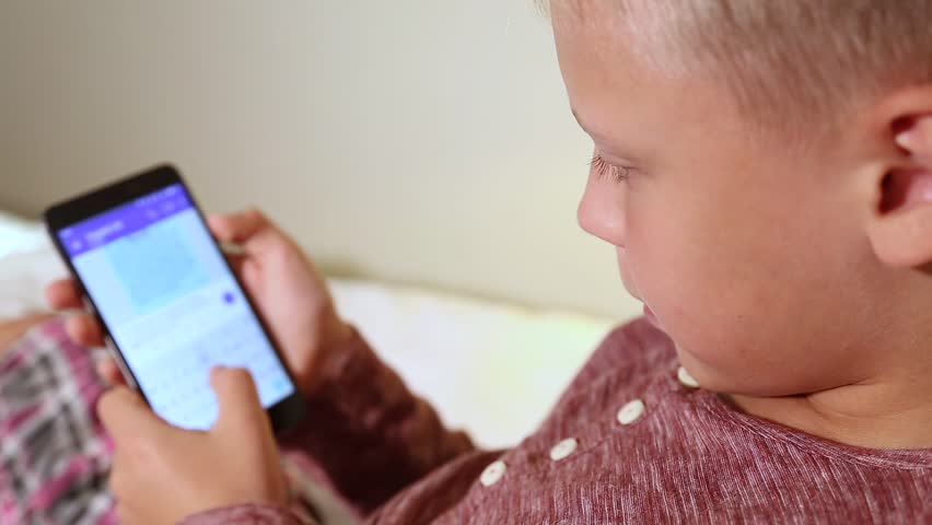 Little kid texting messages at social media application using his black mobile smartphone. Focus at eyes, blurry touch screen. | Shutterstock HD Video #35010220
