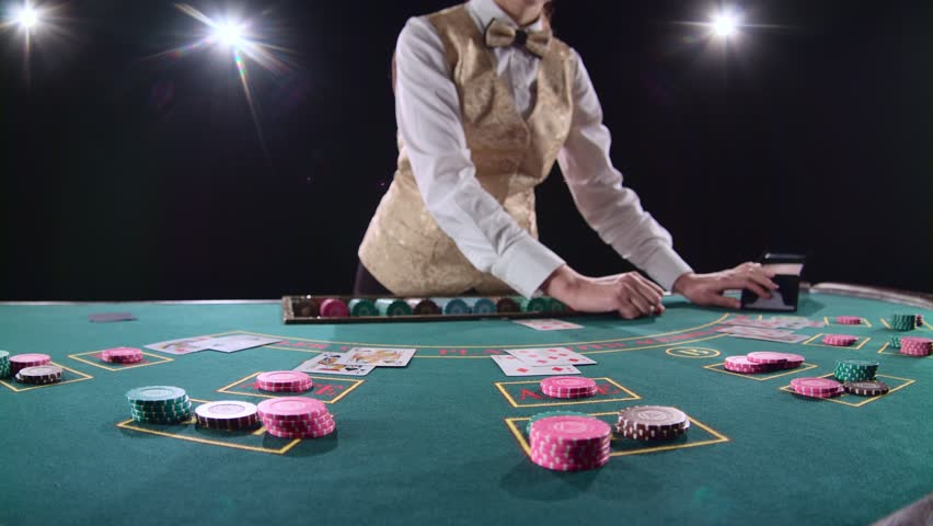Casino croupier distributes for table poker three cards are the flop. Black background. Bright light. Slow motion