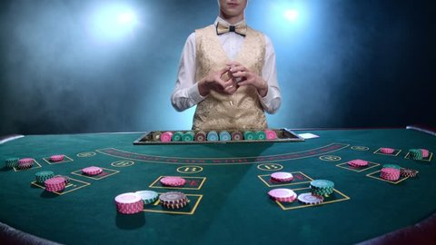 Casino croupier girl shuffles the poker cards and performing trick with cards. Smoke. Slow motion
