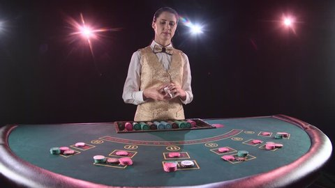 Casino dealer woman shuffles the poker cards and performing trick with cards. Black background. Slow motion