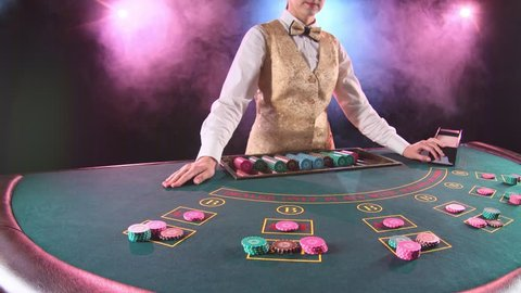 Casino stickman woman in gold vest takes the cards from card holder for game in poker. Black background. Smoke. Slow motion