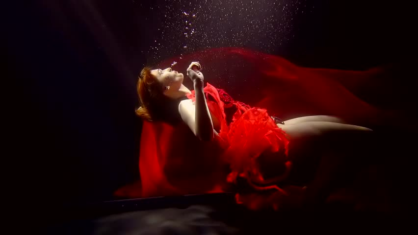 Fascinating woman with pale skin dressed in a luxurious red dress floating up from the darkness.