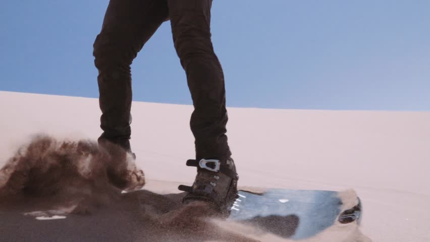 Detail of man making tricks  with a sandboard at the Sand Dunes of the Dead Valley, Atacama desert. Slow motion