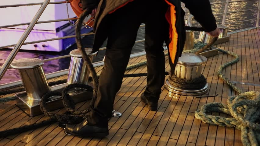 Man coils mooring ropes on deck after river voyage